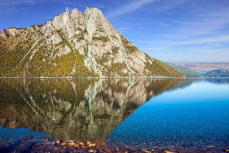 Picturesque pyramidal mountain in the city of San Carlos de Bariloche. The mirror water of the lake reflects sharp peaks and rocks