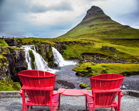 Red paired chaise lounges for rest. Summer in Iceland. The concept of exotic and ecological tourism. Cascading waterfall Kirkjoufellfoss at the foot of the mountain Kirkjoufell