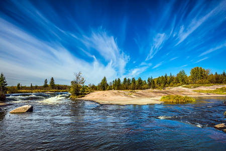 Thin cirrus clouds and foam water rapids on the Winnipeg River. Trend of travel Around the World. Old Pinawa Dam Provincial Heritage Park