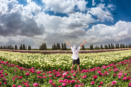 Stunned tourist in white shirt and bandana greets the rising sun. Flower kibbutz near Gaza Strip. Spring flowering buttercups