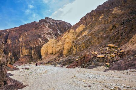 Israel in January. Multi-color Black canyon in ancient Eilat mountains. The elderly woman walking along the canyon