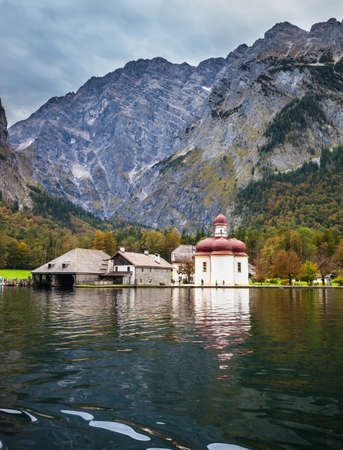 dome of the rock: Picture taken from on board tourist boats. The concept of active tourism. Magic Monastery of St. Bartholomew at Lake Königssee. Red domes of the church reflected in the water