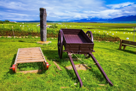 reconstituted: The reconstituted village - Pioneer Museum - Vikings in Iceland. Old wooden sledge and two-wheeled cart on the lawn Stock Photo