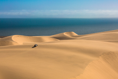 Gorgeous and dangerous  - safari through the huge sand dunes on the ocean coast. The concept of exotic and extreme tourism. Atlantic coast of Namibia, south of Africa