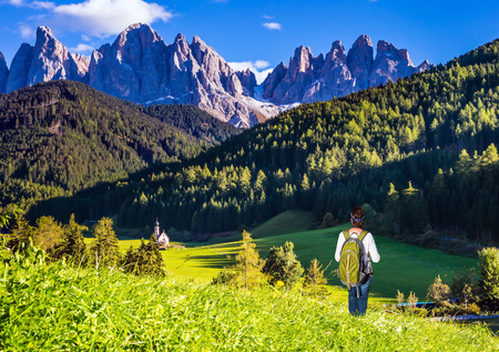 Woman-tourist with backpack admire nature. Sunny day in Dolomites, Tirol. Forested mountains surrounded by green Alpine meadows. The concept of an active and eco-tourism Banco de Imagens