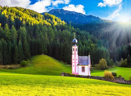 The summer sunset, Dolomites, Tyrol. The famous church of St. Mary Magdalene and bell tower in a mountain valley. The concept of eco-tourism