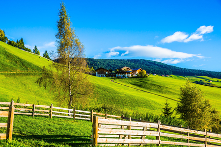 The wooden fence along rural pasture. Concept of eco-tourism. Summer sunset in the Dolomites, Tirol