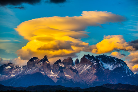 The black-and-steel color of the cliffs of Los Cuernos. Magnificent orange clouds in the rays of the sunset. The concept of extreme and active tourism. Torres del Paine National Park Stock Photo
