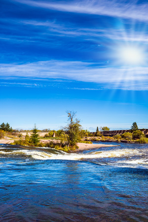 cirrus: The concept of recreational and ecological tourism. Indian summer in Manitoba, Canada. Plumose clouds and autumn sun over the river Winnipeg