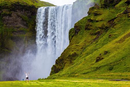 vómito: Gran cascada Skogafoss en Islandia. Turista en camisa y bandana lanzó sus manos con deleite la belleza de la naturaleza