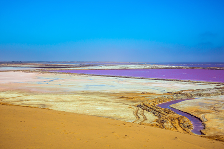 Extraction of ocean salt in Walvis Bay. The concept of ecological and exotic tourism. Multicolored fields for evaporation of water in Namibia