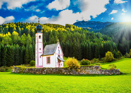 The summer sunset, Dolomites, Tirol. The famous church of St. Mary Magdalene and bell tower in a mountain valley. The concept of eco-tourism Stock Photo
