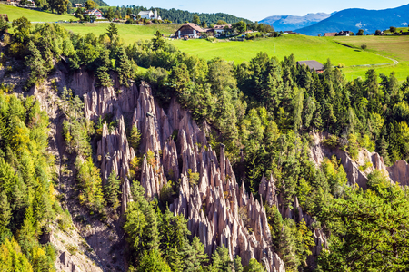 The concept of world tours. Renons earth pillars at sunrise. Small mountain village in the Italian Tirol. Journey to the magic country