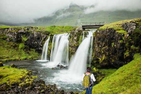 Cascading waterfall Kirkjoufellfoss. Summer in Iceland. Elderly woman -  traveler with a large backpack admiring the waterfall. Concept of exotic and extreme tourism Stock Photo