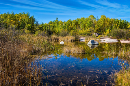 Old Pinawa Dam Provincial Heritage Park. Warm silent day. Yellow autumn grass is reflected in the Winnipeg River. The concept of ecological and recreational tourism Stock Photo