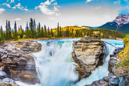 The concept of extreme and ecological tourism. The waters of a melting mountain glacier feed the booming waterfall of Athabasca. Travel to Jasper Park, Canada. Clear autumn evening at sunset