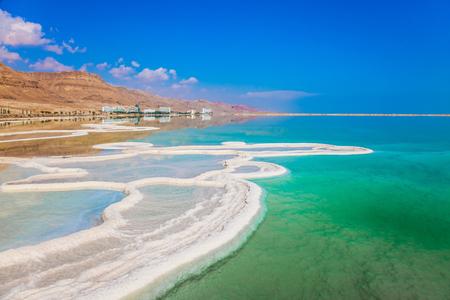 El agua muy salada se ilumina con luz turquesa. El concepto de turismo ecológico y médico. La sal evaporada se ha desarrollado en patrones fantásticos