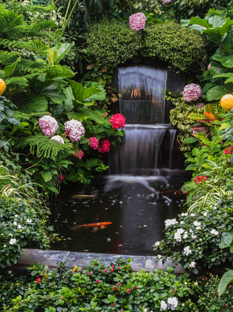 surrounded: Butchart Garden Park on Vancouver Island, Canada. Gorgeous three-stage fountain surrounded by flowers