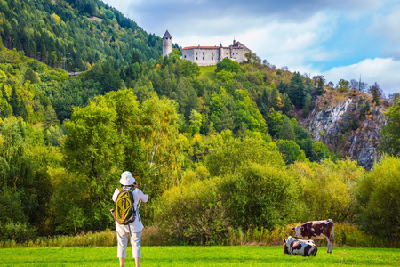 Warm autumn in the Val de Funes, Dolomites. Elderly woman - tourist with backpack travels and   takes pictures in Tyrol. The concept of active and ecotourism Stock Photo