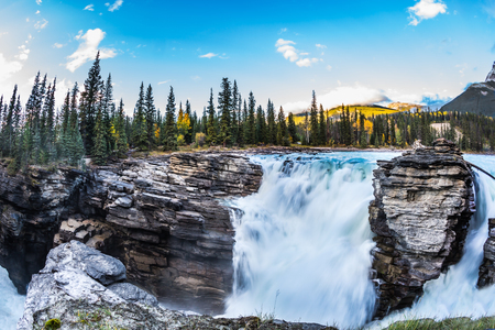Travel to Jasper Park, Canada. The waters of a melting mountain glacier feed the seething waterfall of Athabasca. The concept of ecological tourism