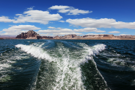 Lake Powell on the Colorado River. Stormy trace of motor boat crossing the emerald waters. In the distance the coast of red sandstone Stock Photo