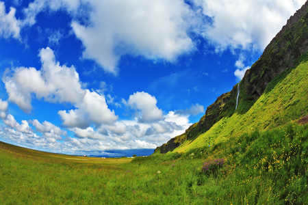Green meadows and cloud sky. Warm summer days in Iceland Stock Photo
