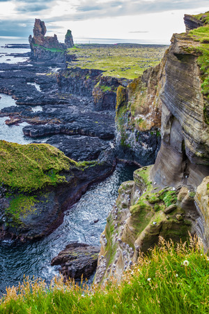 travel features: Magnificent Iceland. Northern sea coast. Picturesque ancient Skerries in cloudy summer day