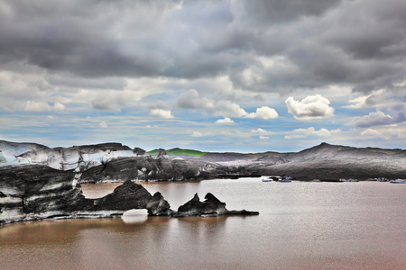 uninhabited: Ice covered with volcanic ash. Mirror Lake, formed as a result of thawing of a glacier Vatnajokull glacier spurs. Iceland in July. Skaftafell National Park