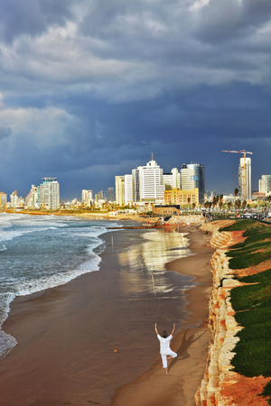 Storm cloud hanging over the sea, the woman in white performs yoga on one leg. Promenade and beach in Tel Aviv Stock fotó