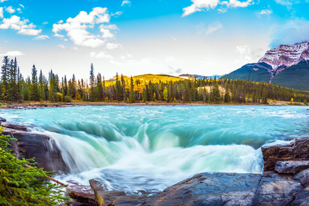 Travel to Jasper Park, Canada. The waters of a melting mountain glacier feed the booming waterfall of Athabasca. Clear autumn evening at sunset. The concept of extreme and ecological tourism
