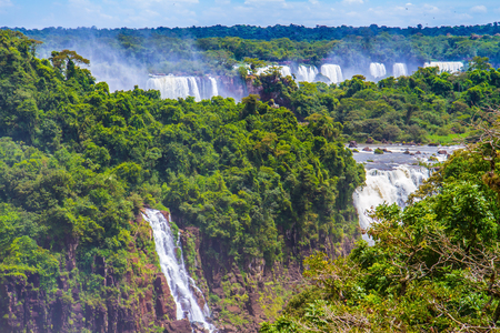 The fantastic roaring Iguazu Falls in South America, on the border of three countries: Brazil, Argentina and Paraguay. Concept of active and extreme tourism