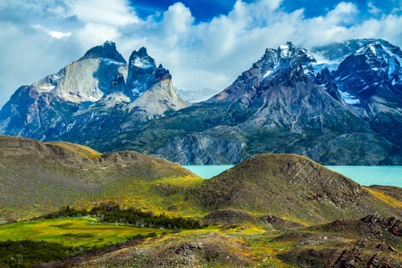 Travel in Chile. National Park Torres del Paine. Strong wind drives the heavy gray clouds above the cliffs of Los Kuernos. The concept of active and adventure tourism