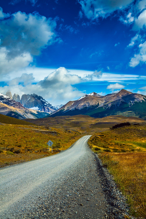 Gravel road in the Torres del Paine National Park. Summer in the south of Chile. The mountains and rocks are covered with snow and ice.  The concept of automobile extreme tourism