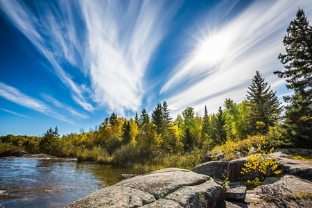 Incredible cirrus clouds  and huge flat stones in Old Pinawa Dam Park. Indian summer in Manitoba, Canada. The concept of ecological and recreational tourism Stock Photo