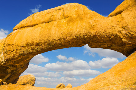 Natural group of smooth bald granites among the Namib Desert. Stone arch of Spitzkoppe, Namibia. Concept of extreme and ecological tourism