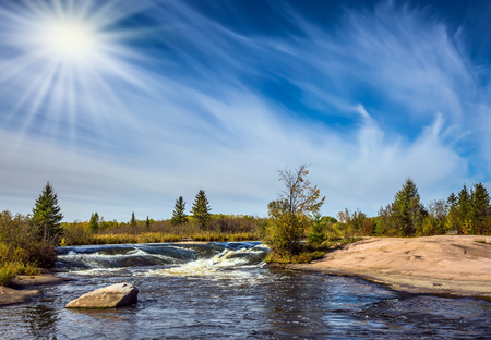 cirrus:  Waterfall drain on the smooth stones of the Winnipeg River. Weak northern autumn sun. The concept of ecological and extreme tourism tourists Stock Photo