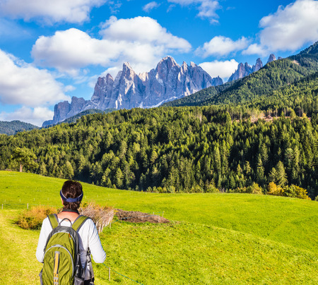 Elderly woman - tourist with backpack travels in Tyrol. Warm autumn in the Val de Funes, Dolomites. The concept of active and ecotourism