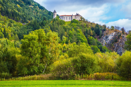 val: Medieval castle on the crest of the mountain. The concept of ecological tourism. Charming green   forest of the mountain. Val de Funes, Dolomites. Warm autumn day