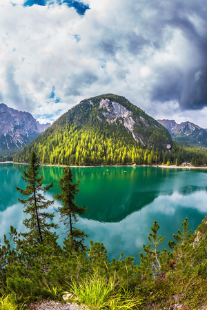 expanse: The concept of walking and eco-tourism. Green water reflects the surrounding forest and mountains. Magnificent lake Lago di Braies. South Tyrol, Italy