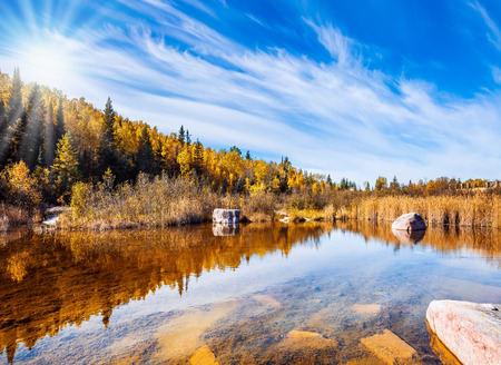 Old Pinawa Dam Park. The concept of travel Around the World. Yellow autumn grass and pale northern sun is reflected in the Winnipeg River Stock Photo