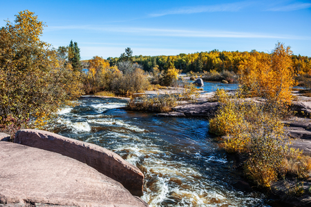 Warm clear autumn day. Foam water rapids on the smooth stones of the Winnipeg River. The concept of ecological tourism