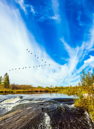 Foam water rapids on the smooth stones of the Winnipeg River. Cirrus clouds . The concept of travel Around the World. Old Pinawa Dam Provincial Heritage Park, Canada