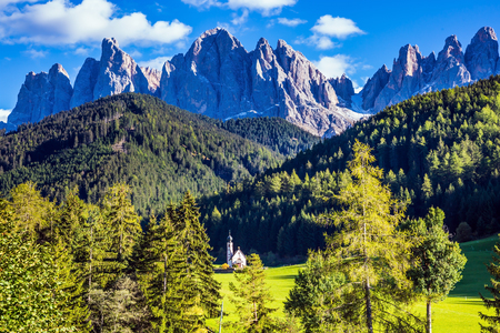 Dolomites, Tirol. Sunny warm autumn day. Rocky peaks and forested mountains surrounded by green Alpine meadows. The symbol of the valley Val di Funes - church of Santa Maddalena Banco de Imagens