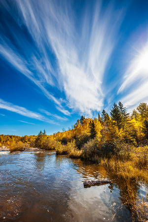 Incredible cirrus clouds over the Winnipeg River. Indian summer in Manitoba, Canada. Old Pinawa Dam Park. The concept of ecological and recreational tourism Stock Photo