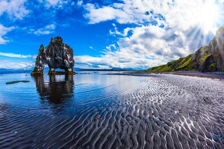 Basalt rock - monster Hvitsercur ocean low tide. Concept of northern extreme tourism. Soft northern sun of Iceland at sunset