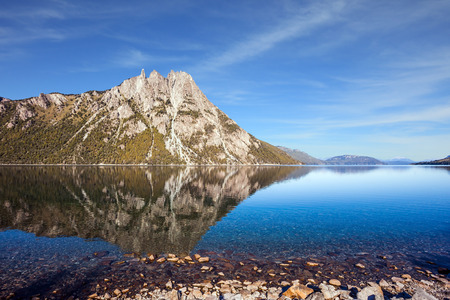 Picturesque pyramidal mountain in the city of San Carlos de Bariloche. The mirror water of the lake reflects sharp peaks and rocks. The concept of exotic and extreme tourism