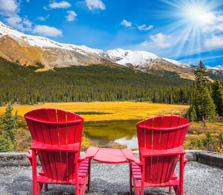 Two red comfortable chaise longue in a swampy valley. The beautiful nature in northern Rocky Mountains of Canada
