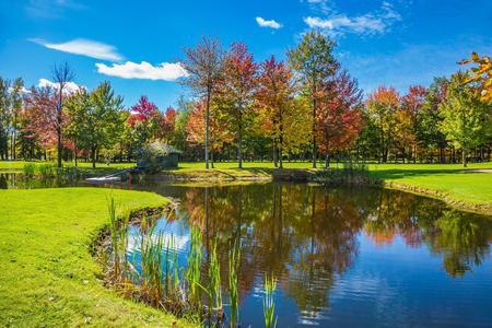 아주 좋은 공원. Bromont, 프랑스 캐나다에 도로에 골프 클럽. 골프 관광의 개념입니다. 빨강, 오렌지 및 녹색 단풍이 호수의 맑은 물에 반영됩니다