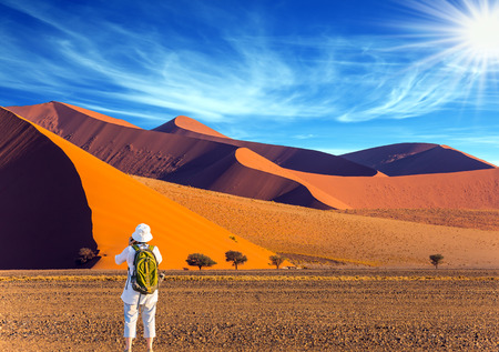 Elderly enthusiastic woman with a green backpack is taking pictures of a magnificent landscape. Orange, purple and yellow dunes of the Namib desert. The concept of extreme and exotic tourism Stock Photo