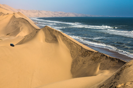 Ocean surf with foamy waves. Dangerous jeep - safari through the huge sand dunes. Atlantic coast of Walvis Bay, Namibia, south of Africa. The concept of extreme and exotic tourism